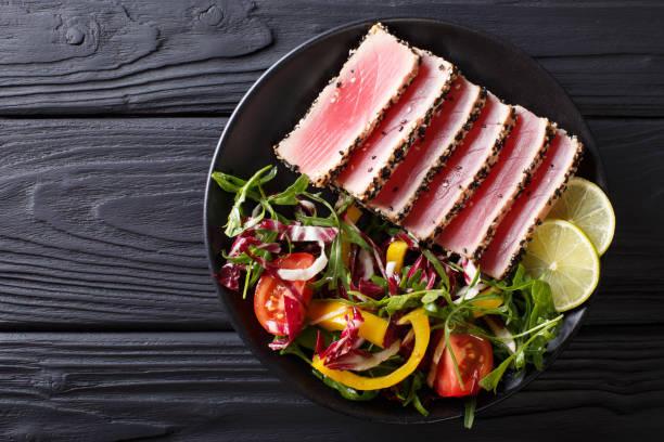 nahaufnahme von seltenen gebratene ahi thunfisch-scheiben mit salat aus frischem gemüse. horizontale ansicht von oben - steak anbraten stock-fotos und bilder