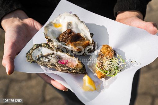 Close up of raw, fried, and smoked gourmet oysters at a street food market fair festival