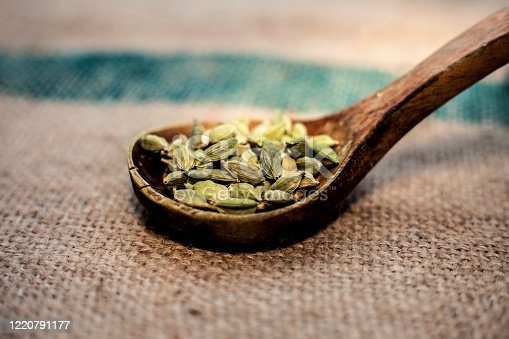Close up of raw green colored fresh Cardamom, cardamon, cardamum or ealichi in a wooden scoop on a brown colored surface.