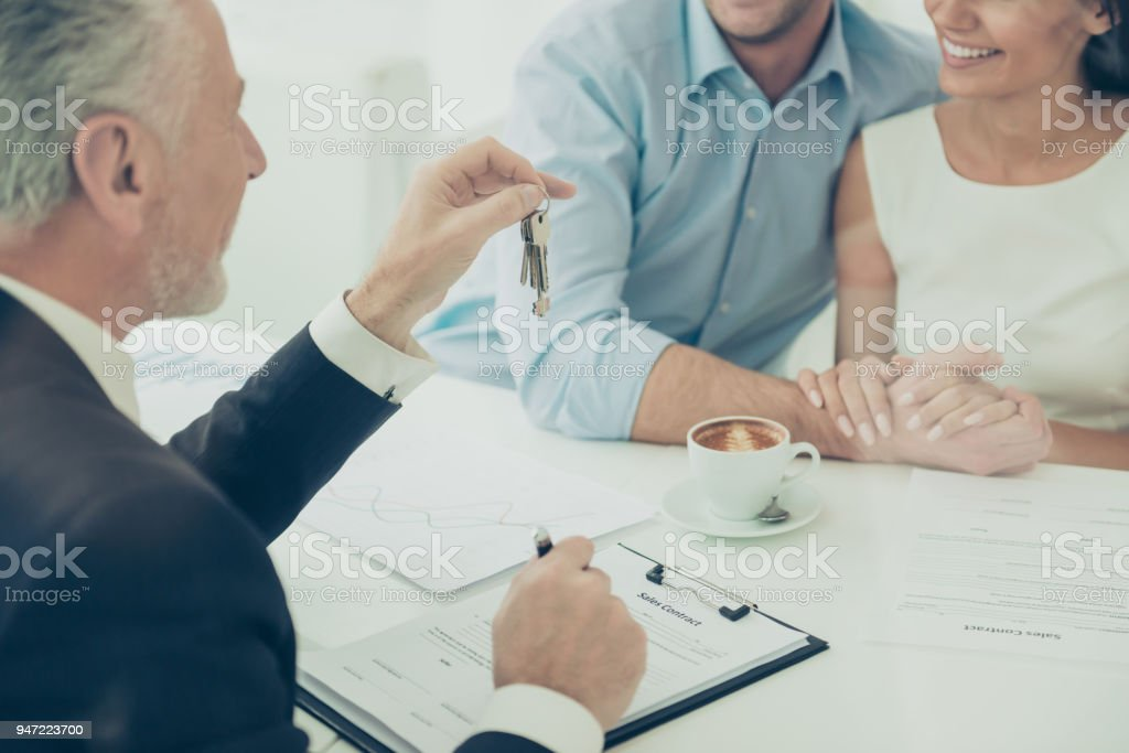Close up of real estate agent giving keys to couple of customers stock photo