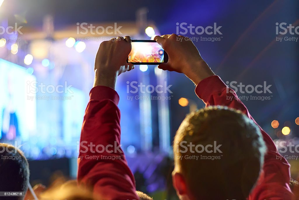 Close up of recording video with smartphone during a concert. stock photo