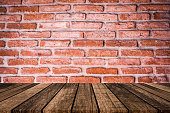 close up of red and brown brick stone cement wall background textured with aged wood tile floor for advertisement or promote product , content on display concept