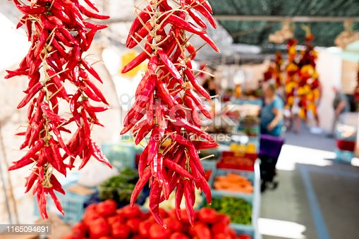 close up of red hor chili pepper hangin at organic farmers market stalls with people in background during sunny summer day