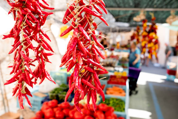 close up of red hor chili pepper hangin at organic farmers market stalls with people in background during sunny summer day stock photo