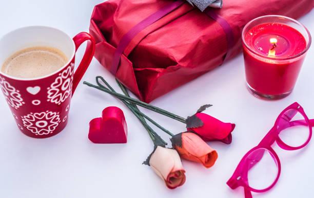 primer plano de las cosas rojas. vacaciones para personas enamoradas. día de san valentín. taza roja con café, flores de rosa, regalo y vela - happy couple sharing a cup of coffee fotografías e imágenes de stock