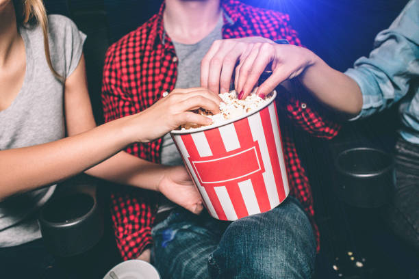 Close up of red with white basket of popcorn that both girl and guy are holding. All of them are taking popcorn out of basket. Ð¡ut view. Close up of red with white basket of popcorn that both girl and guy are holding. All of them are taking popcorn out of basket. Ð¡ut view movie theater stock pictures, royalty-free photos & images