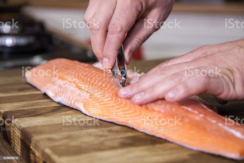 Close up of removing fish bone from salmon. stock photo