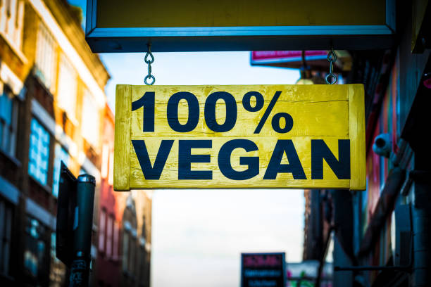Close up of restaurant sign outdoors on city street saying 100% vegan stock photo
