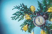 Close up of retro alarm clock on Christmas background with green branch and garland. Retro toned, flat lay, copy space.