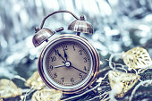 Close up of retro alarm clock on blurred Christmas background with bokeh