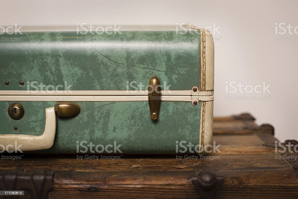 Close Up of Retro, Green Suitcase, Sitting on Wood Trunk stock photo