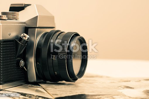 609706398 istock photo Close up of retro photo camera with old photographs. 609706210