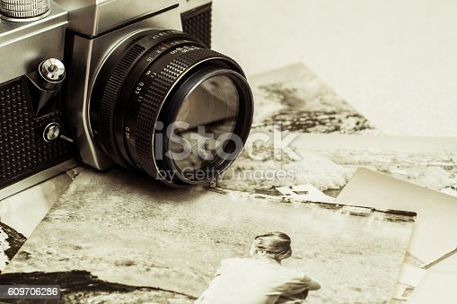 609706398 istock photo Close up of retro photo camera with old photographs. 609706286