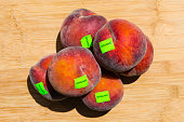 Close up of ripe peaches, carrying organic stickers, on a wooden board background