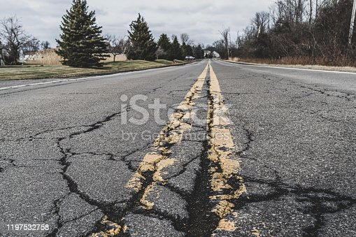 Close up of road markings and cracked asphalt of a suburban road.  Grand Island, New York.