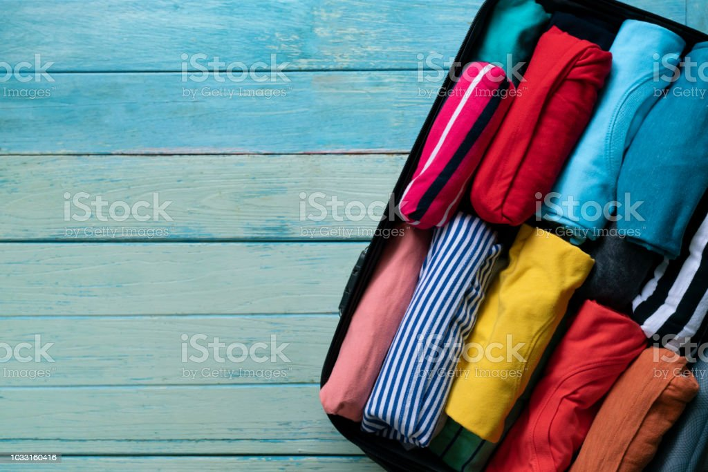 close up of rolled colorful clothes in a luggage for a new journey stock photo