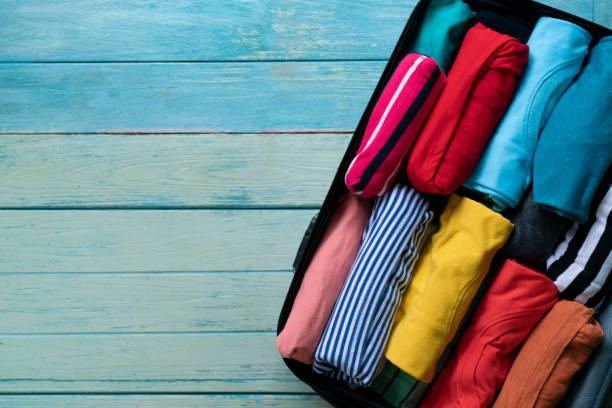 nahaufnahme von gewalzten bunte kleidung im gepäck für die reise - kleidung falten stock-fotos und bilder