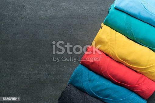 istock close up of rolled colorful clothes on black background 673929544