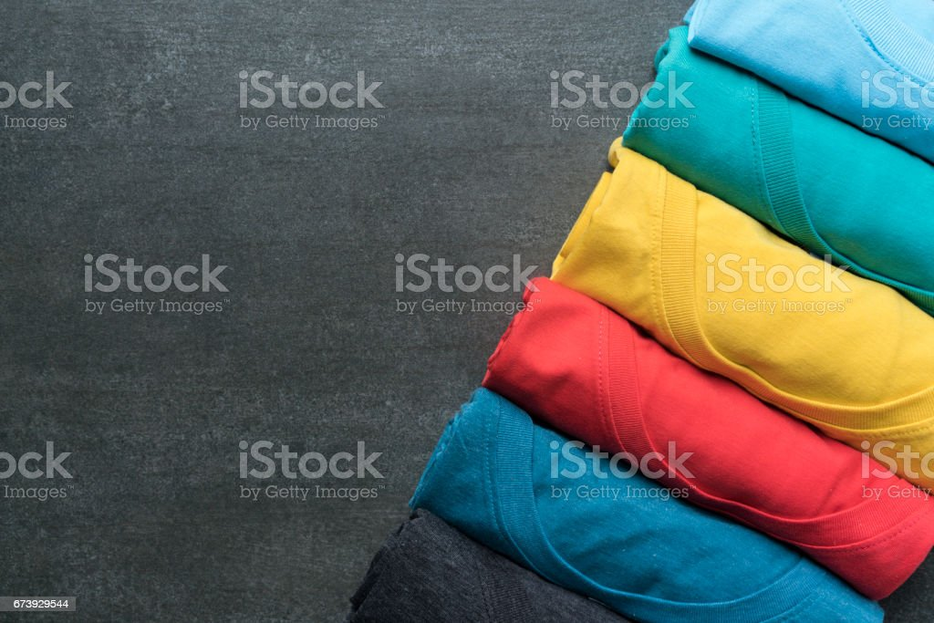 close up of rolled colorful clothes on black background stock photo