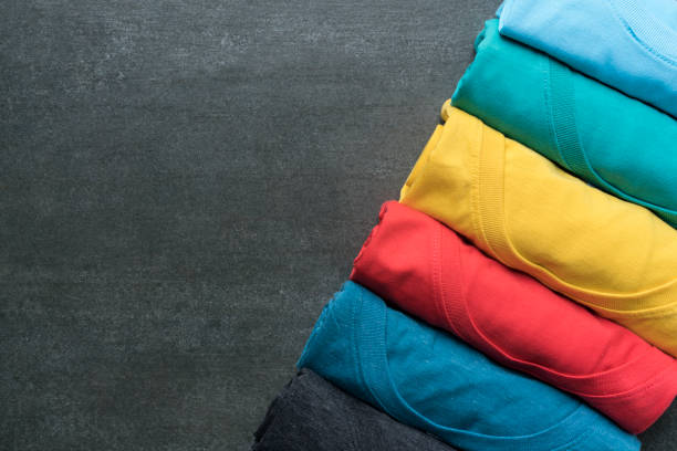 close up of rolled colorful clothes on black background - t shirt stock photos and pictures