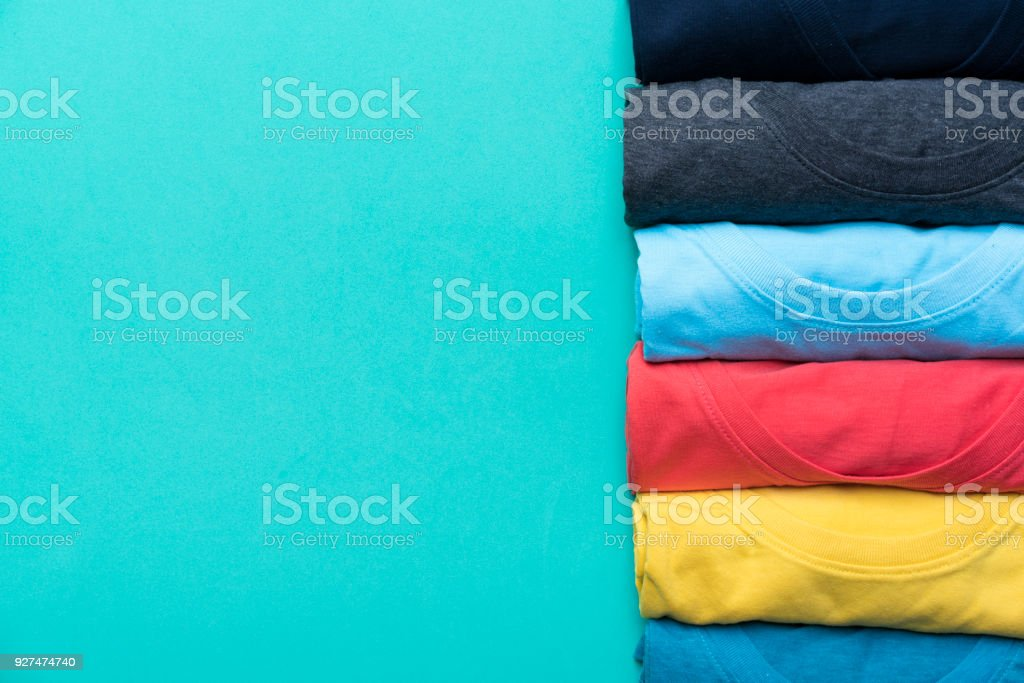 close up of rolled colorful clothes on green background stock photo