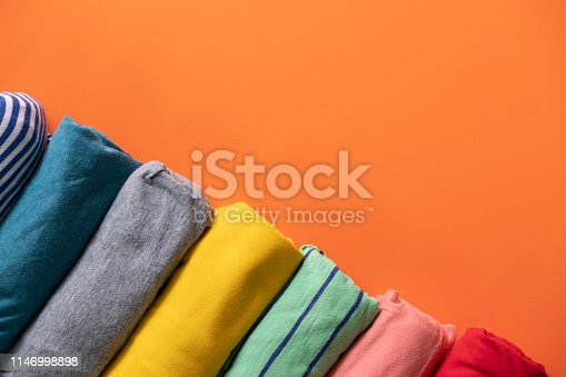 close up of rolled colorful clothes on orange background
