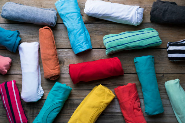 close up of rolled colorful clothes on wooden table background stock photo