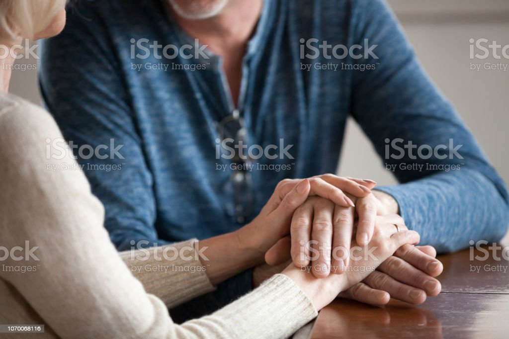 Close up of romantic aged couple holding hands caressing Close up of sensual aged husband and wife holding hands enjoying romantic moment at home, caring senior couple caress and comfort each other, having tender sincere talk. Elderly love concept Adult Stock Photo