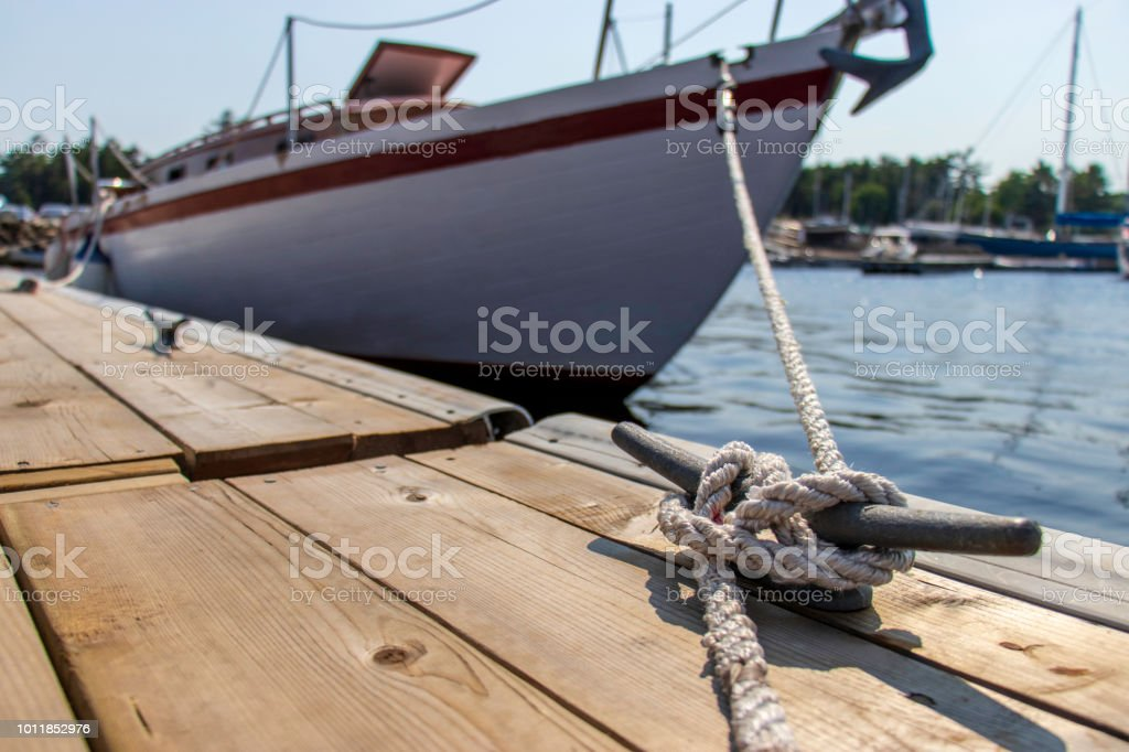 Close up of rope tied to a cleat securing the bow of a sailboat to a dock. stock photo