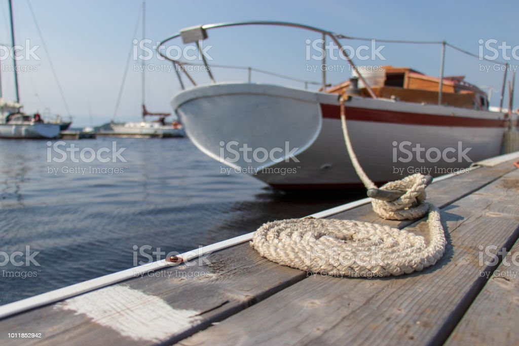 Close up of rope tied to a cleat securing the stern of a sailboat to a dock. stock photo