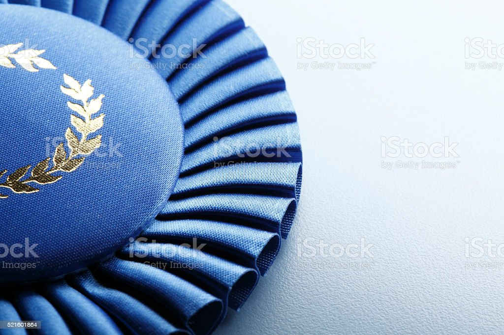 A close up of a rosette from a first place blue ribbon. The image is...
