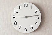 白い壁紙の家の壁に丸い時計のクローズ アップ