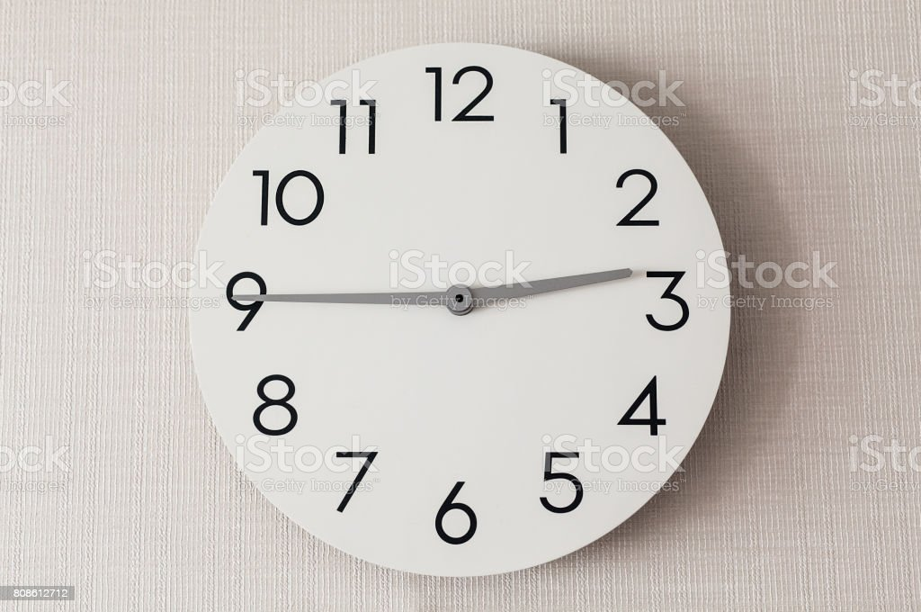 close up of round clock on wall with white wallpaper in house stock photo