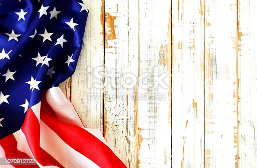 istock Close up of ruffled American flag over grunged wooden wall with a lot of copy space. 1070912722