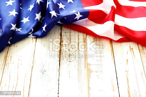 istock Close up of ruffled American flag over grunged wooden wall with a lot of copy space. 1070912744