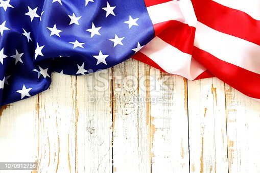 istock Close up of ruffled American flag over grunged wooden wall with a lot of copy space. 1070912756