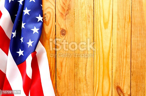 istock Close up of ruffled American flag over wooden wall with a lot of copy space. 1070912878