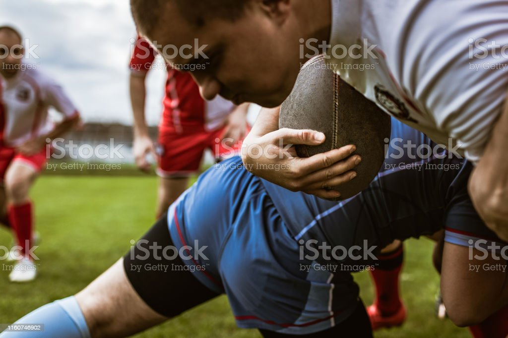 Close up of rugby player gripping through defensive player on a match...