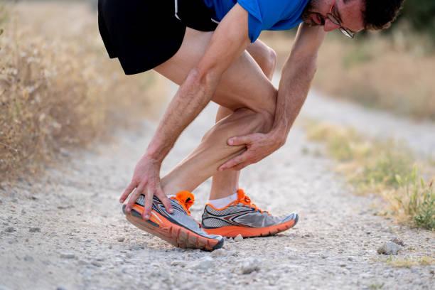 痛みを伴うツイストまたは壊れた足首新やふくらはぎアスリート ランナー訓練事故スポーツ実行中足首捻挫の概念に触れてランナーのクローズ アップ - 脛 ストックフォトと画像