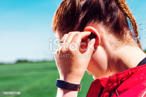istock Close up of runner wearing wireless earbuds and listening to music or a podcast 1002802108