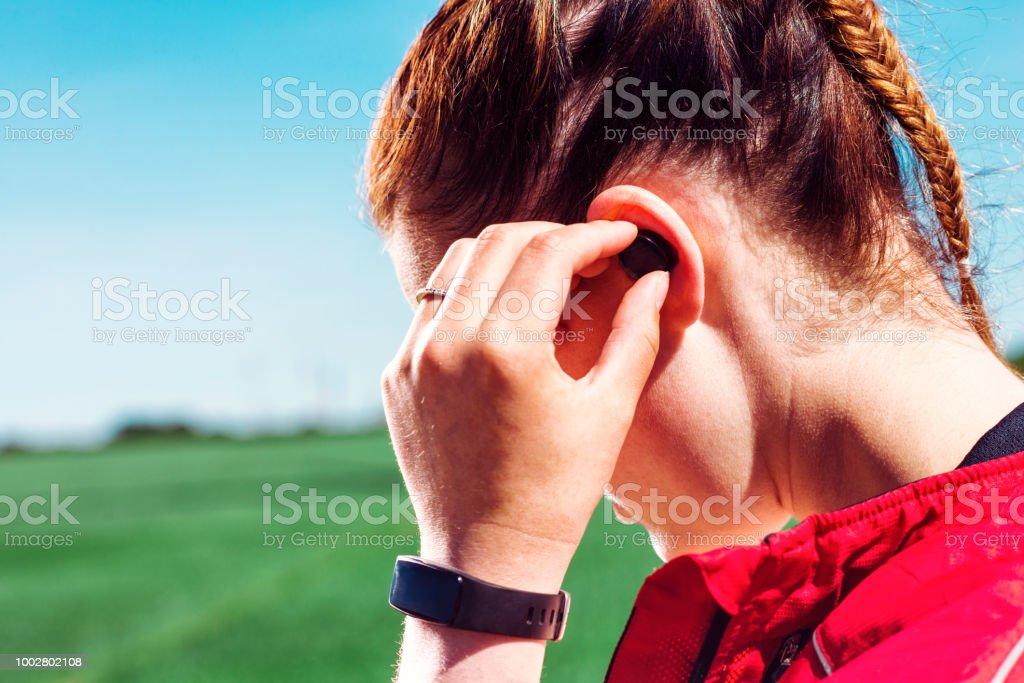 Close-up do corredor usando fones de ouvido sem fio e ouvindo música ou um podcast - foto de acervo