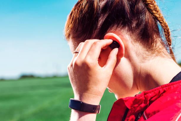 gros plan du coureur portant des écouteurs sans fil et écouter de la musique ou un podcast - écouteurs intra auriculaires photos et images de collection