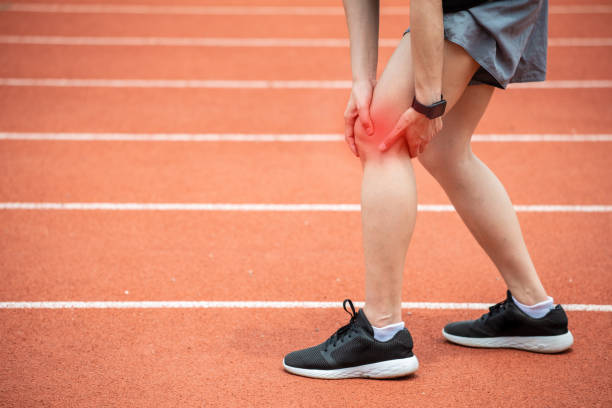 Close up of runner woman holding her leg, suffuring from ITB Syndrome in sport track. ITB Syndrome caused by altered running biomechanics due to underlying muscular imbalances. suffragist stock pictures, royalty-free photos & images