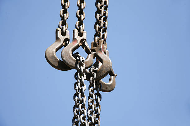 Close up of rusted hanging chain and blue sky Close up of hanging chain and crane hook against blue sky rigging stock pictures, royalty-free photos & images