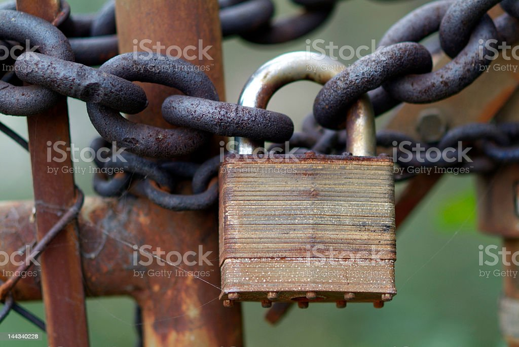 Close up of rusted lock and chain holding rusted fence royalty-free stock photo