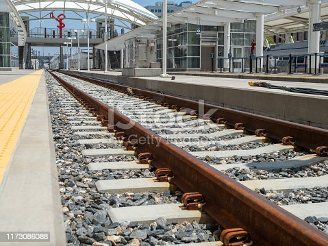 Close up of rusty railroad travels and gravel in a modern train station