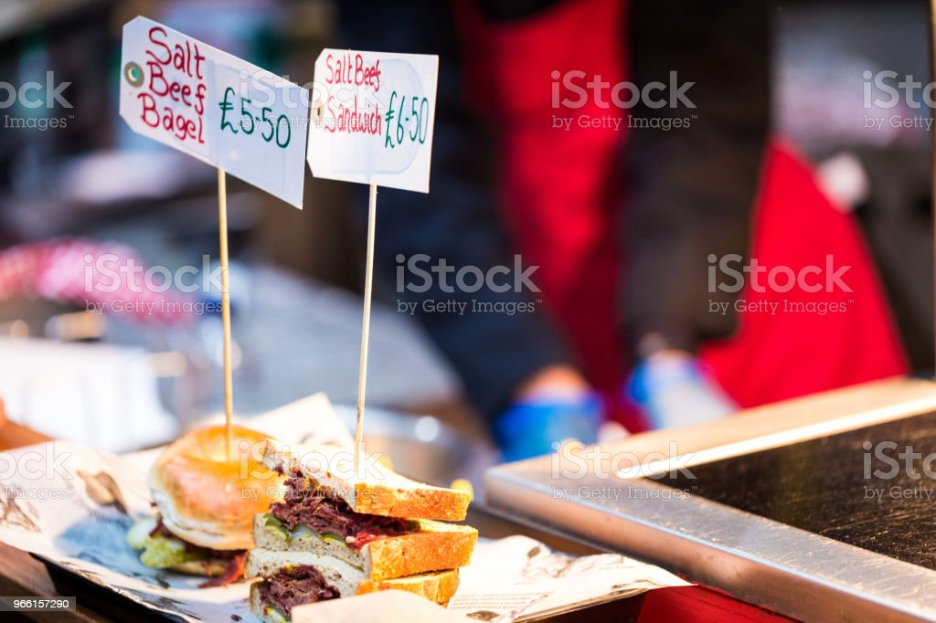Närbild på salt nötkött senap smörgåsar och bagels med kocken i bakgrunden - Royaltyfri Bagel Bildbanksbilder