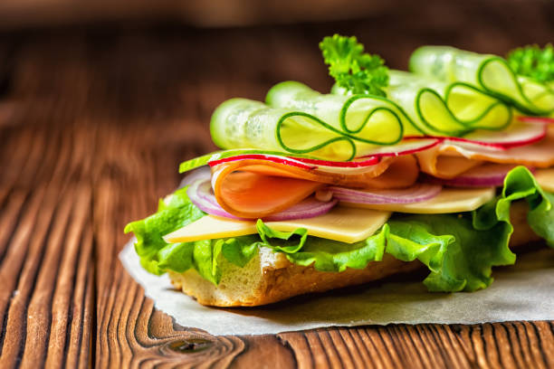 close up of sandwich with ham, cheese, bacon, radish, lettuce, cucumbers and onions on paper, wooden background - panino ripieno foto e immagini stock