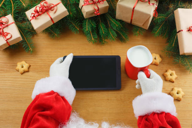 Close up of Santa Claus hands holding blank digital tablet with copy space stock photo