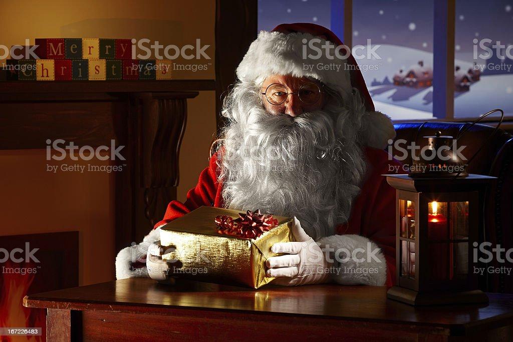 close up of Santa holding a christmas gift stock photo